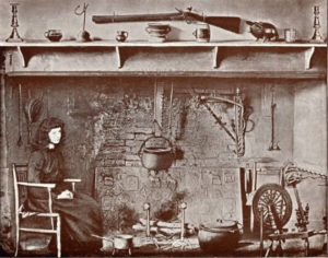 A woman sitting at a fireplace containing a fireback